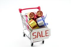 Boxes with gifts and kegs with figures 2019/ in a cart from a supermarket. royalty free stock photography