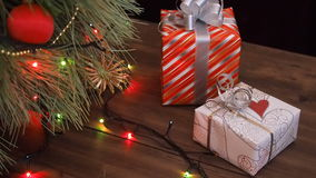 Boxes of gifts are under the tree. Gifts are Packed in colorful paper and tied with string and ribbons. Christmas. Gifts boxes under the tree. Gifts are Packed stock video
