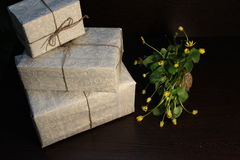 Boxes with gifts and wild flowers. Boxes with gifts facing each other and wildflowers on a dark background stock photo