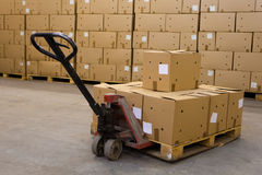 Boxes on hand pallet truck. Cardboard boxes on hand pallet truck in the storehouse Stock Photography