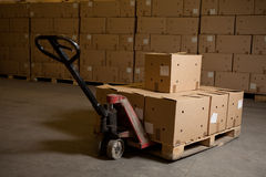 Boxes on hand pallet truck. Boxes standing on hand pallet truck in the storehouse Royalty Free Stock Images