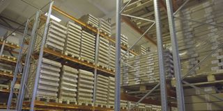 Boxes on high shelves at industrial warehouse on production plant drone view. Large warehouse of finished products from stock image