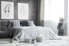 Drawings in bright bedroom interior. Boxes near bed with grey bedsheets against concrete wall with drawings in bright bedroom interior royalty free stock image