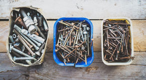 Boxes of old rusty metal screws on wooden background Stock Photography