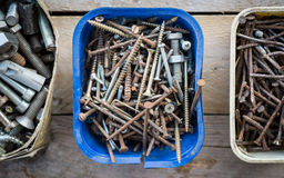 Boxes of old rusty metal screws on wooden background Royalty Free Stock Photos