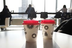 2 boxes of paper disposable cups with red led on the table in the cafe. Morning. Coffee for Breakfast. Coffee to go. The shadows stock photo