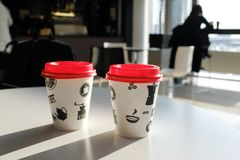 2 boxes of paper disposable cups with a red lid on the table in the cafe. Coffee to go. Morning. Coffee for Breakfast. 2 cups of stock photo