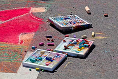 Boxes of Pastels With Sidewalk Art. Boxes spilling out art pastels used for sidewalk art sitting on the ground next to bright red drawings stock photography