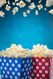 Boxes of popcorn on blue background. Royalty Free Stock Photo