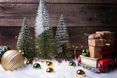 Boxes with presents in toy car, decorative fir trees, golden and green balls and fairy lights royalty free stock photography