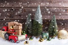 Boxes with presents in toy car, decorative fir trees, golden and green balls and fairy lights royalty free stock photos