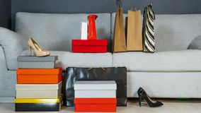 Boxes with shoes and shopping bags on the background of a gray sofa royalty free stock image