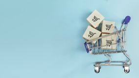 Boxes in a shopping cart on blue background. Concept: online shopping, e commerce and delivery of goods. Copy space royalty free stock photography