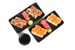 Boxes with tasty sushi rolls and bowl of soy sauce on white background, top view. Food delivery stock photography