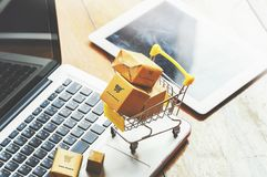 Boxes in a trolley on a laptop keyboard. Ideas about online shopping stock images