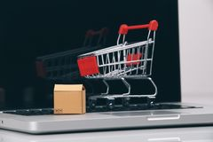 Boxes in and trolley on a laptop online shopping is a form of electronic commerce that allows consumers to directly buy stock photo