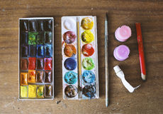Boxes with watercolors on wooden background Stock Photo