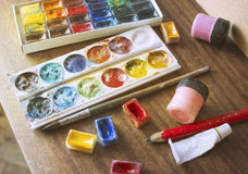 Boxes with watercolors on wooden background Royalty Free Stock Photos