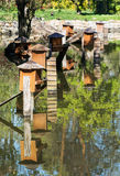 Boxes for waterfowl nesting are mirrored in the water Royalty Free Stock Photo