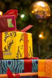 Bright Christmas presents by the Xmas tree. Boxes of xmas presents near christmas tree Stock Images