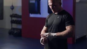 Boxeur brutal enveloppant des mains avec les bandages élastiques avant combat, mouvement lent Sc?ne de faible luminosit? banque de vidéos