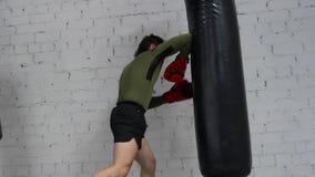 Boxeur d'homme dans les gants poinçonnant le sac de combat par des genoux et des coudes dans le club de boxe Coup-de-pied s'exerç clips vidéos