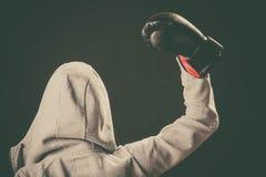 Boxeur dans le support de hoodie vers l'arrière avec la main en air Image libre de droits