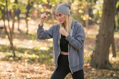 Boxeur de fille faisant le coup-de-pied d'uppercut établissant dehors photographie stock libre de droits