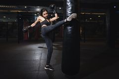Boxeur féminin frappant un sac de sable énorme à un studio de boxe Boxeur de femme s'exerçant dur Coup-de-pied thaïlandais de poi image stock