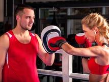 Boxeur féminin jetant la bonne croix aux gants Image stock