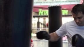 Boxeur faisant quelques séances d'entraînement sur un sac de sable dans le gymnase MOIS lent banque de vidéos