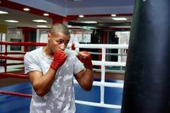 Boxeur frappant un sac de sable énorme à un studio de boxe Boxeur s'exerçant dur photo libre de droits