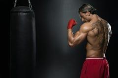Boxeur musculaire sans chemise avec le sac de sable dans le gymnase images libres de droits