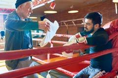 Boxeur prenant le repos sur l'anneau avec l'entraîneur image libre de droits