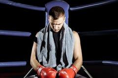 Boxeur professionnel musculaire de coup-de-pied se reposant sur les cordes dans le coin de l'anneau tout en s'exerçant pour le pr images libres de droits