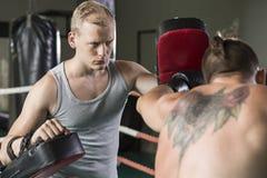Boxeur s'exerçant avec l'entraîneur images stock