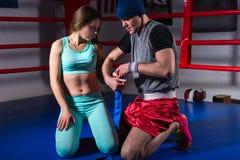 Boxeur sportif masculin préparant des bandages pour la jeune femelle photo libre de droits