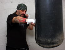 Boxing. A man with tattoo training boxing indoor Stock Image