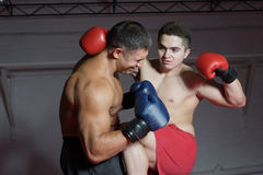 Boxing. Two boxers train in a gym against a dark background Stock Photo