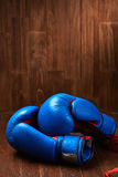Boxing background with blue gloves and red bandage on wooden background. Royalty Free Stock Images