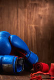 Boxing background with blue gloves and red bandage on wooden background. Stock Image