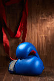 Boxing background with gloves and red bandage against wooden background. Stock Image