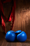 Boxing background with gloves and red bandage against wooden background. Stock Photos