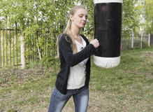 Boxing beautiful young blond girl punches a heavy bag Stock Photography