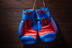 Boxing blue and red gloves hanging from ropes on a wooden background. Stock Photography