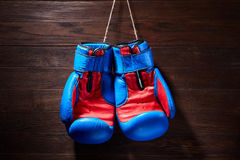 Boxing blue and red gloves hanging from ropes on a wooden background. Royalty Free Stock Photos