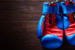Boxing blue and red gloves hanging from ropes on a wooden background. Horizontal photo of the bright sportwear against brown wall. Boxing backgrounds and still stock images