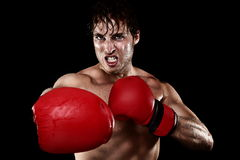 Boxing boxer. Man with boxing gloves hitting and punching looking angry. Strong muscular fit fitness model showing competition strength. Caucasian male model stock photos