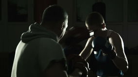 The boxing coach trains the young boxer stock video footage
