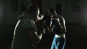 The boxing coach trains the young boxer stock video